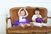 Beautiful little girl in purple skirt and crown and her friend sitting on couch