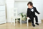 Little boy in black suit sitting on white chair and looks at next chair