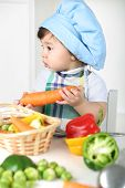 Little boy with serious face in kitchen apron and cap holding carrot