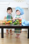 Little girl in kitchen apron and cap and boy standing at table with vegetables