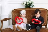 Little beautiful lady in white long dress and boy in black suit sitting on couch with hearts