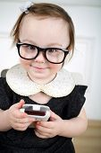 foto of lurex  - Portrait of smiling little girl in black dress and glasses with mobile phone in hands - JPG
