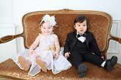Beautiful little kids in costumes bride and groom sitting on couch