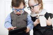 picture of lurex  - Little girl in glasses and black dress with mobile phone next to serious boy with tablet computer - JPG