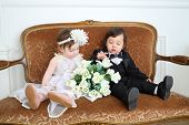 Beautiful little kids in costumes bride and groom sitting on couch with bouquet of flowers