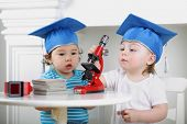 stock photo of graduation hat  - Small children in blue graduation hat adjust microscope on table - JPG