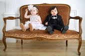 Little girl in beautiful white dress and serious boy in black suit sitting on couch