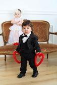 Little boy in black suit with hearts and beautiful girl in white long dress on couch