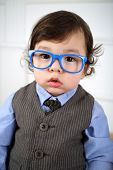 Portrait of serious little boy in striped vest and blue glasses