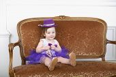 Beautiful little girl in purple skirt and hat sitting on couch