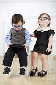 Little boy with tablet computer sitting on white chair next to happy girl with glasses