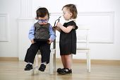 foto of lurex  - Little boy with tablet computer sitting on white chair next to girl in black dress with glasses - JPG