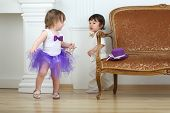 Little girl in purple skirt running away from boy in white suit around sofa