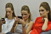 NOVOSIBIRSK, RUSSIA - NOVEMBER 15, 2014: Models with their phones waiting for fashion show during Novosibirsk Fashion Week. The event was held under the motto High Fashion & High Classics