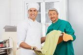 Portrait of confident male chefs holding green spaghetti pasta sheet at commercial kitchen