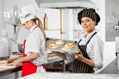 Happy female chef holding small pizzas on tray with colleague working in background at commercial kitchen