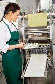 Side view of female chef preparing ravioli pasta in machine at commercial kitchen
