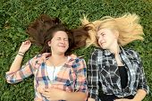 Blonde and brunette friends lying on grass
