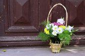 Flowers in basket on wooden door background