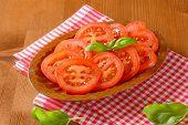 bowl of tomato slices and fresh basil on checkered dishtowel