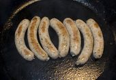 Sausages in frying pan.