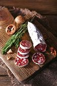 French salami on cutting board on sackcloth napkin on wooden background