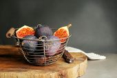 Ripe sweet figs in metal basket, on wooden table, on dark background