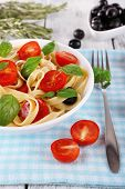 Spaghetti with tomatoes, olives and basil leaves on plate on napkin on wooden table