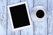 Tablet and cup of coffee on wooden background