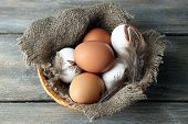 Eggs in basket, on wooden background. Organic food concept
