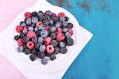 Iced berries on plate, on color wooden background