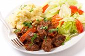 Beef in red sauce with a salad and mashed potato wand a fork