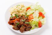 Beef in red sauce with a salad and mashed potato
