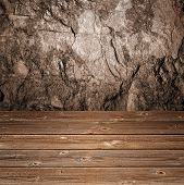 Grungy textured stone background behind wooden perspective floor