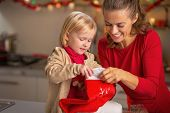 Portrait Of Happy Mother And Baby With Christmas Stocking In Kit