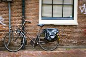 Traditional dutch bicycle parked on near brick wall in Amsterdam