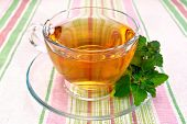 Tea with mint in cup on tablecloth