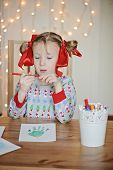 Cute little girl making Christmas handprints postcard