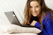 Smiling Girl At Laptop Over Sofa