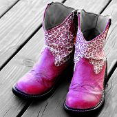 Detail of pink cowgirl cowboy boots on wood deck for a girl