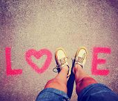 two feet making a sign for the letter V in the word love toned with a retro vintage instagram filter effect