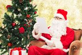 christmas, holidays and people concept - man in costume of santa claus with letter over yellow lights background