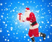 christmas, holidays and people concept - man in costume of santa claus running with gift box over blue snowy background
