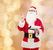 christmas, holidays, gesture and people concept - man in costume of santa claus with notepad pointing finger up over beige lights background
