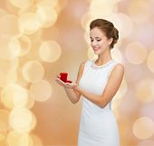 wedding, love, engagement and people concept - smiling woman in white dress holding red gift box with diamond ring over beige lights background