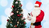 holidays, technology and people concept - man in costume of santa claus with smartphone, presents and christmas tree over blue lights background