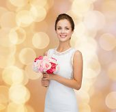 people, wedding, holidays and celebration concept - smiling bride or bridesmaid in white dress with bouquet of flowers over beige lights background