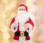 christmas, holidays, food, drink and people concept - man in costume of santa claus with glass of milk and cookies over beige lights background