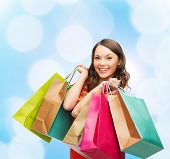 sale, gifts, christmas, holidays and people concept - smiling woman with colorful shopping bags over blue lights background