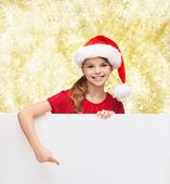 christmas, holidays, people, advertisement and sale concept - happy little girl in santa helper hat with blank white board over yellow lights background